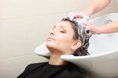 在理发沙龙。发式专家洗涤的头发妇女客户。 免版税库存图片