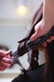 在理发沙龙。女性头发和调直铁。 库存照片