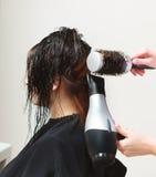 在理发沙龙。有妇女客户的更加干燥的干毛发的发式专家。 库存照片