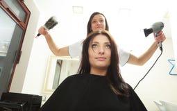 在理发沙龙。有妇女客户的更加干燥的干毛发的发式专家。 免版税库存图片