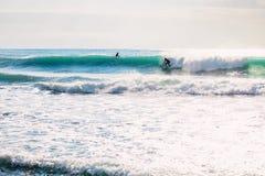 在理想的蓝色波浪的冲浪者乘驾 冲浪在海洋的冬天 免版税库存照片