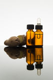 在琥珀色的瓶的姜精油有姜根和吸管的 免版税库存照片