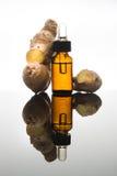 在琥珀色的瓶的姜精油有姜根和吸管的 免版税库存图片