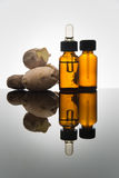 在琥珀色的瓶的姜精油有姜根和吸管的 库存照片