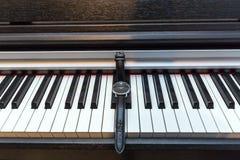 在琴键的手表 时间和音乐的概念 免版税库存照片