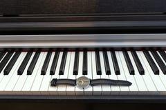 在琴键的手表 时间和音乐的概念 库存照片