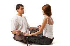 在瑜伽位置的健康夫妇在白色 免版税库存照片