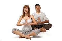 在瑜伽位置的健康夫妇在白色 库存照片