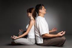 在瑜伽位置的健康夫妇在黑暗 库存图片