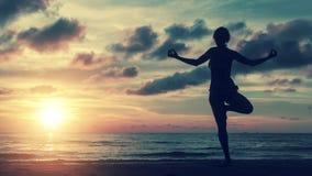 在瑜伽姿势的女孩剪影在海的海滩 库存图片