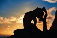 在瑜伽姿势的妇女剪影在日落海海滩 免版税库存图片