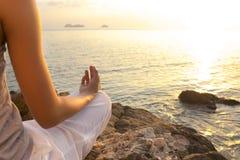 在瑜伽姿势的少妇凝思在热带海滩 免版税库存照片