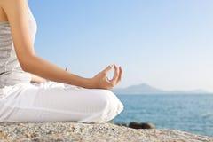 在瑜伽姿势的少妇凝思在热带海滩 免版税库存图片