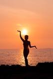 在瑜伽姿势的常设妇女剪影在被点燃的海背景 免版税库存图片