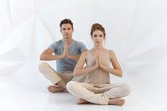 在瑜伽姿势的年轻夫妇 免版税库存照片