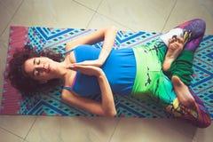 在瑜伽席子的妇女谎言用在namaste姿态和腿的手 库存照片