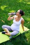 在瑜伽席子的孕妇饮用水在公园 库存照片