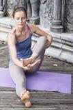 在瑜伽撤退期间的少妇实践的瑜伽在亚洲,巴厘岛,凝思,在被放弃的寺庙的放松 库存图片