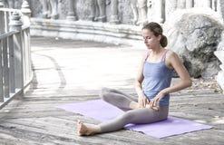 在瑜伽撤退期间的少妇实践的瑜伽在亚洲,巴厘岛,凝思,在被放弃的寺庙的放松 免版税库存图片
