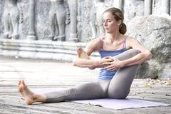 在瑜伽撤退期间的少妇实践的瑜伽在亚洲,巴厘岛,凝思,在被放弃的寺庙的放松 免版税库存照片