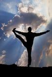 在瑜伽树姿势的人平衡在海洋海滩 图库摄影