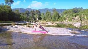 在瑜伽的夫人立场摆在手边倾斜在河中 影视素材