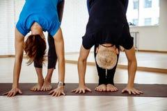 在瑜伽过程中的两名妇女 免版税库存图片