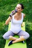 在瑜伽锻炼以后的渴孕妇饮用水 免版税图库摄影