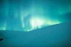在瑞典多雪的山的极光borealis 图库摄影