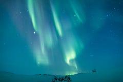在瑞典多雪的山的极光borealis 库存照片