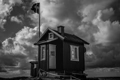 在瑞典旗子前面的一个小小屋 免版税库存图片