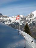 在瑞士阿尔卑斯前面的瑞士旗子在冬天 免版税图库摄影