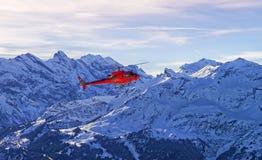 在瑞士阿尔卑斯的红色直升机在少女峰山附近 免版税库存照片