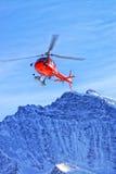 在瑞士阿尔卑斯的红色直升机在少女峰山附近 免版税库存图片