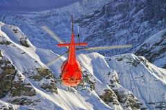 在瑞士阿尔卑斯的红色直升机在少女峰山附近 免版税图库摄影