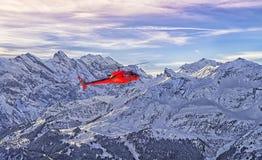 在瑞士阿尔卑斯的红色直升机在少女峰山附近 库存照片
