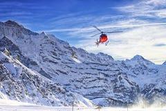 在瑞士阿尔卑斯的红色直升机飞行在少女峰山附近 图库摄影