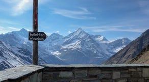 在瑞士阿尔卑斯签署指向洗手间一个山小屋 免版税库存照片