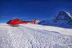 在瑞士阿尔卑斯滑雪胜地的红色直升机在少女峰山附近 免版税库存照片