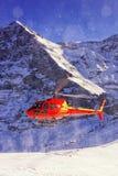 在瑞士滑雪胜地的红色直升机着陆在少女峰mountai附近 库存照片
