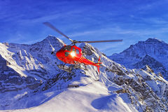 在瑞士滑雪胜地的红色直升机着陆在少女峰mountai附近 免版税库存照片