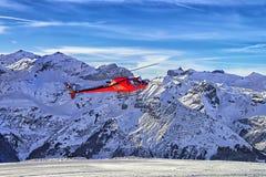 在瑞士滑雪胜地的红色直升机着陆在少女峰mountai附近 免版税库存图片
