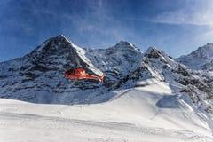在瑞士滑雪胜地的红色直升机着陆在少女峰mountai附近 图库摄影