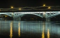 在瓜达尔基维尔河河旁边的美丽的Triana桥梁在它的途中穿过市塞维利亚,安大路西亚 免版税库存照片