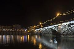 在瓜达尔基维尔河河旁边的美丽的Triana桥梁在它的途中穿过市塞维利亚,安大路西亚 库存图片