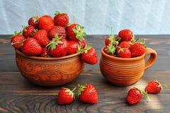 在瓦器的草莓在一张木桌上 o 免版税库存照片