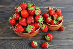 在瓦器的草莓在一张木桌上 免版税图库摄影