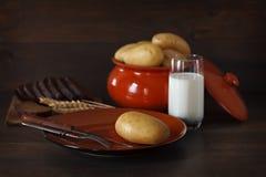 在瓦器的被烘烤的土豆在桌上 免版税库存照片
