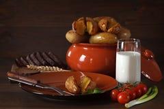在瓦器的被烘烤的土豆在桌上 图库摄影