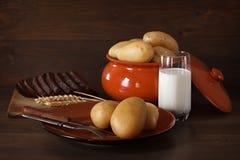 在瓦器的被烘烤的土豆在桌上 免版税图库摄影